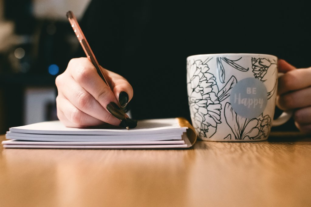 a person writing in their notebook while drinking from a mug