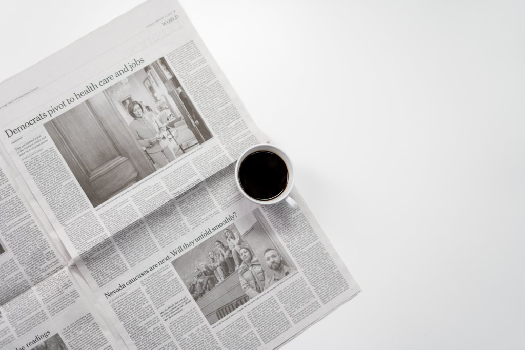 coffee cup sitting on top of an open newspaper