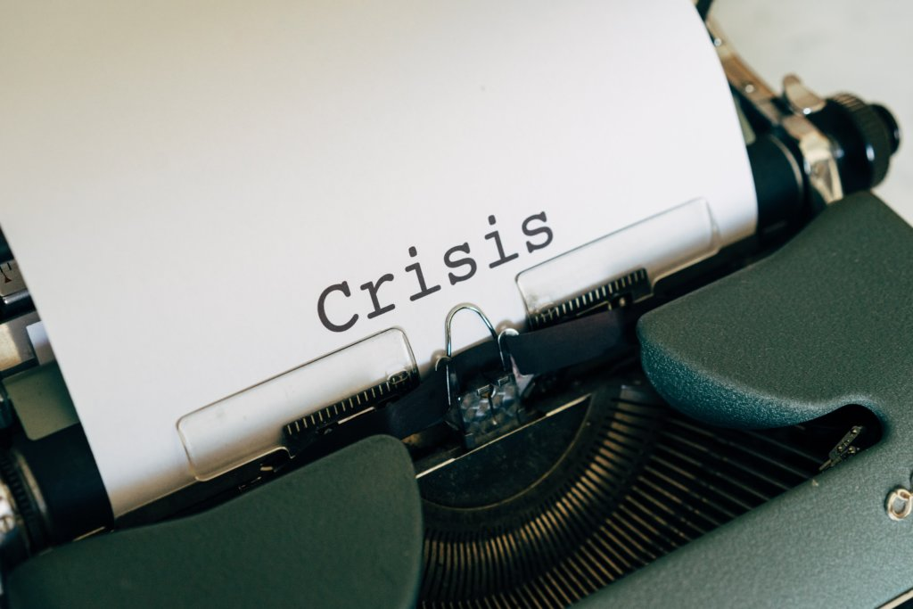 the word crisis written on a piece of paper in a typewriter