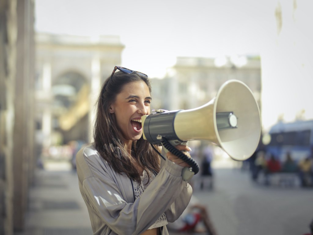 a happy young woman shouting into a megaphone