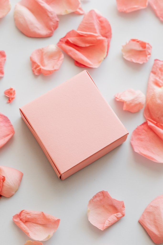 a small pink gift box surrounded by pink flower petals