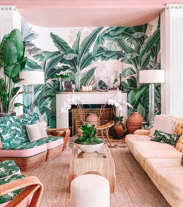 a living room full of plants and patterned furniture